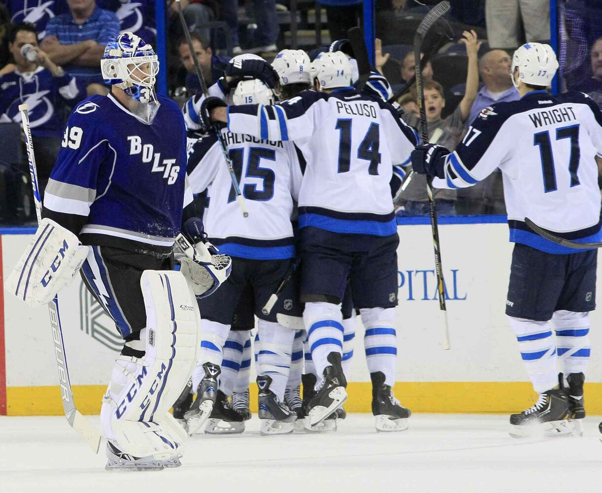 Tampa Bay Lightning goalie Anders Lindback skates off after getting beaten in overtime while the Jets celebrate.
