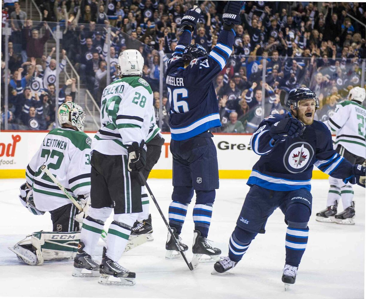 Winnipeg Jets  Bryan Little (#18) and Blake Wheeler (#26) celebrate Andrew Ladd's second-period goal against the Dallas Stars Saturday. (David Lipnowski / Winnipeg Free Press)