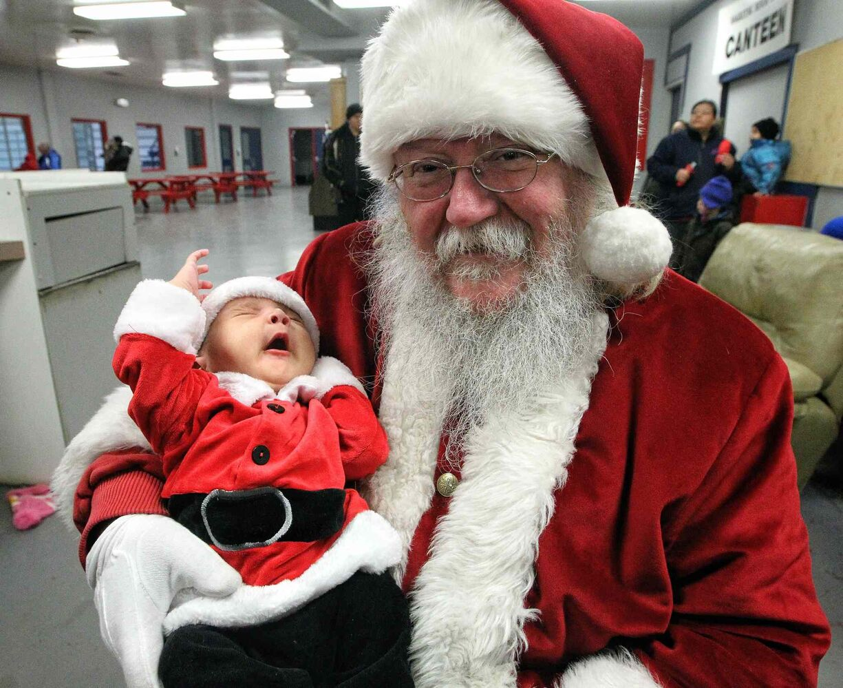 Five-week-old Channing Edwards, dressed like a miniature Santa, gives a huge yawn while visiting Santa at the Sagkeeng Arena Multi-Plex during Santa's visit to the Sagkeeng First Nation.