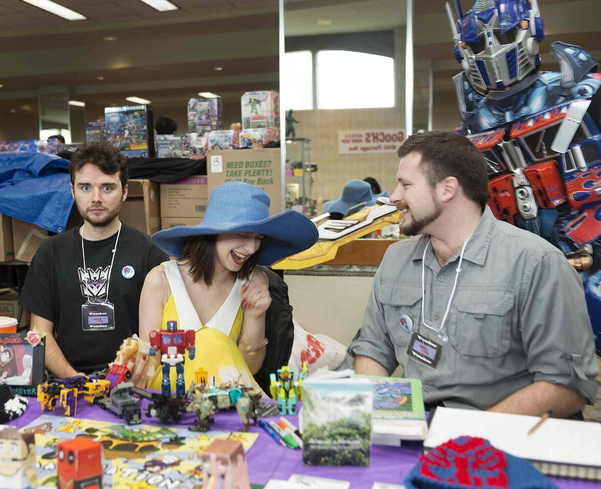 Optimus Prime photobombs William O'Donnell, Stacie Gagnon and Bart Rucinski at their Yak and Shadow vendor at Saturday's Transformers convention in the Clarion Hotel. (Sarah Taylor / Winnipeg Free Press)