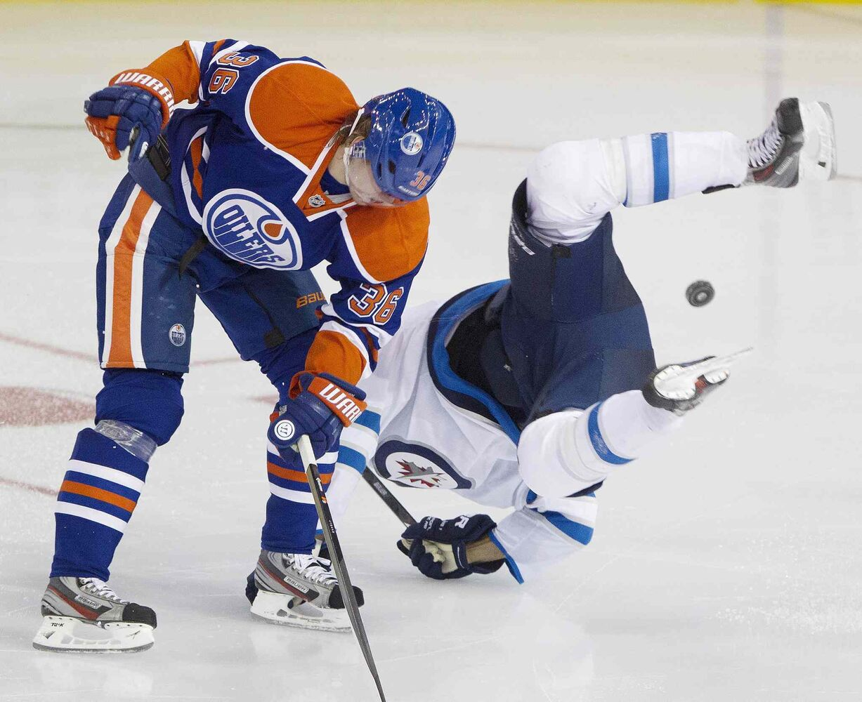 Evander Kane (9) is upended by Edmonton Oilers Philip Larsen (36) during the third period. (Jason Franson / The Canadian Press)