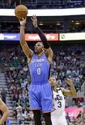 Oklahoma City Thunder guard Russell Westbrook (0) shoots in front of Utah Jazz guard Trey Burke (3) during the first quarter of an NBA basketball game Saturday, March 28, 2015. (AP Photo/Rick Bowmer)