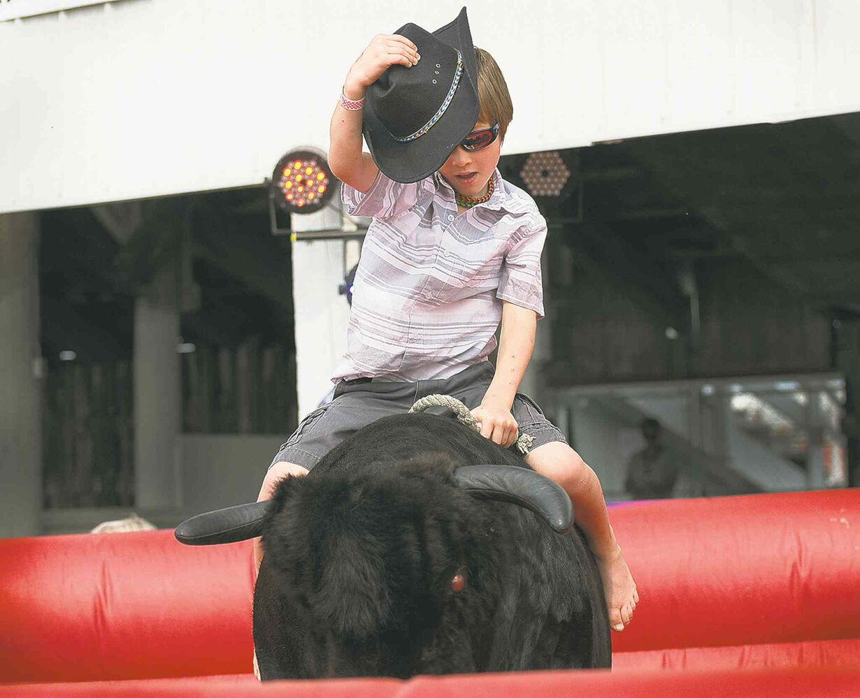 Seven-year-old  Tannet Treichel from Darlingford, Man., channels  his inner cowboy  as he rides the  mechanical bull  at the Morris  Stampede  Thursday. The stampede runs until Sunday. (Sarah Taylor / Winnipeg Free Press)