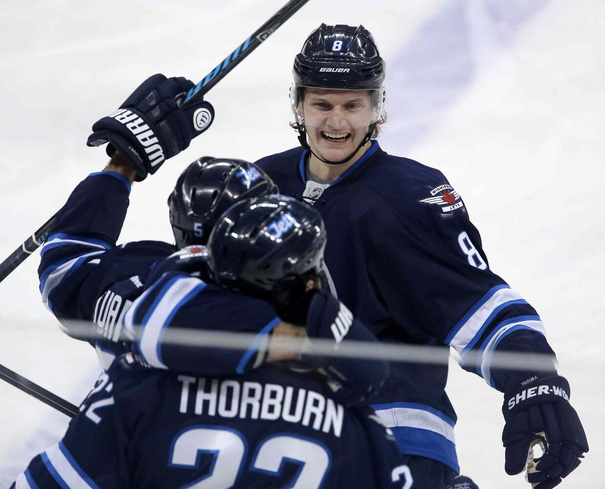 Winnipeg Jets' Jacob Trouba (8), Mark Stuart (5) and Chris Thorburn (22) celebrate Thorburn's first goal of the season during the  first period of Tuesday's game against the Nashville Predators in Winnipeg. (Trevor Hagan / The Canadian Press)