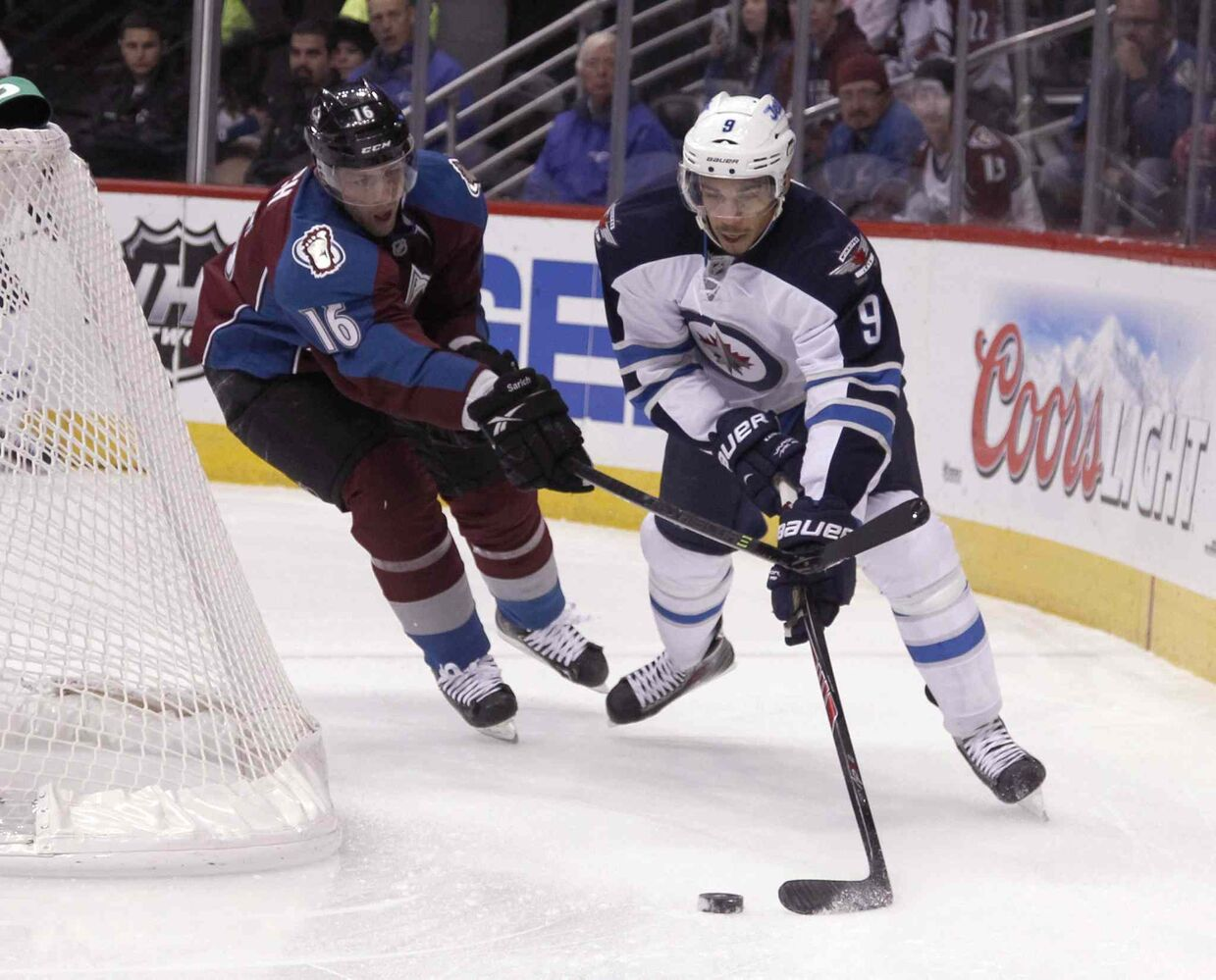 Evander Kane tries a wraparound as Avalanche defenceman Cory Sarich gives chase in the first period. (David Zalubowski / The Associated Press)