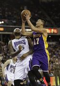 Los Angeles Lakers guard Jeremy Lin, right, goes to the basket against Sacramento Kings center DeMarcus Cousins during the first half of an NBA basketball game in Sacramento, Calif., Sunday, Dec. 21, 2014. (AP Photo/Rich Pedroncelli)