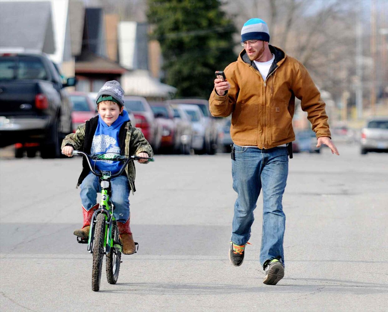 Levi Marez runs alongside his son Kaden Fletcher, 6, left, as he learns to ride the bike he got for Christmas, Wednesday, Dec. 25, 2013, in Henderson, Kentucky.  (The Associated Press)