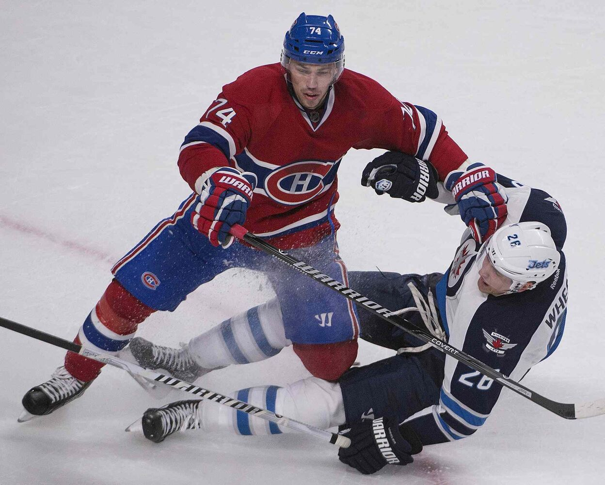 Jets leading scorer Blake Wheeler falls being hit by Montreal Canadiens' Alexei Emelin.