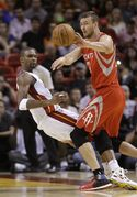 Houston Rockets forward Donatas Motiejunas of Lithuania, right, collides with Miami Heat forward Chris Bosh as he passes the ball during the first half of a preseason NBA basketball game, Tuesday, Oct. 21, 2014 in Miami. (AP Photo/Wilfredo Lee)