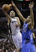 San Antonio Spurs' Tony Parker (9), of France, shoots around Dallas Mavericks' Devin Harris (20) during the first quarter of Game 1 of the opening-round NBA basketball playoff series on Sunday, April 20, 2014, in San Antonio. (AP Photo/Eric Gay)