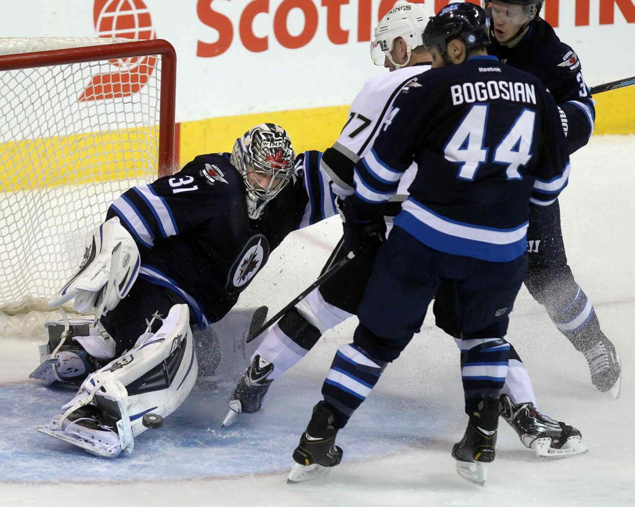 Ondrej Pavelec covers up as Zach Bogosian, Tobias Engstrom and Los Angeles King Jeff Carter slide to a stop in the crease in the third period. (Phil Hossack / Winnipeg Free Press)