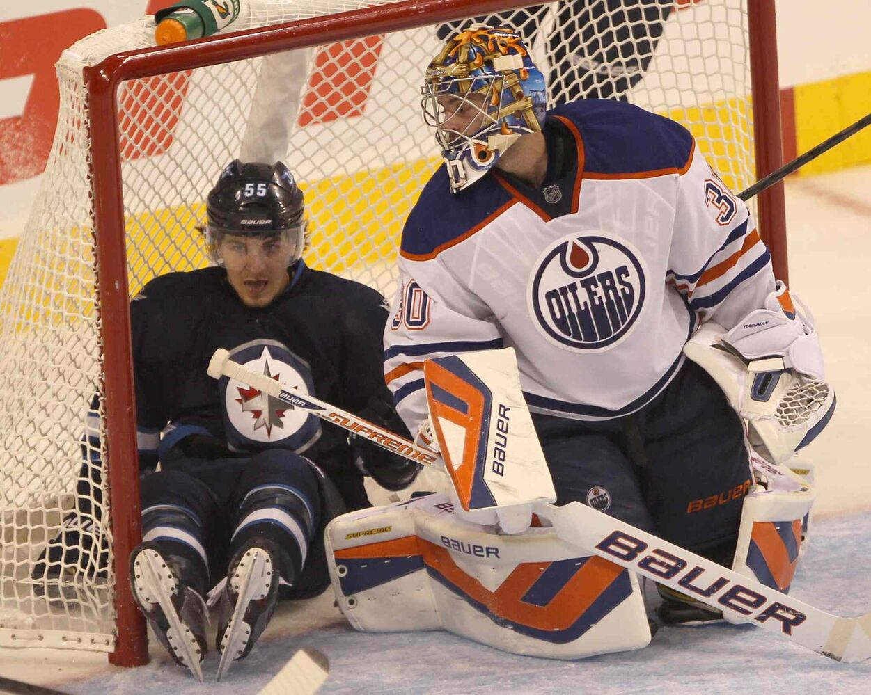 Winnipeg Jets centre Mark Scheifele winds up in the net behind Edmonton Oilers goaltender Richard Bachman.