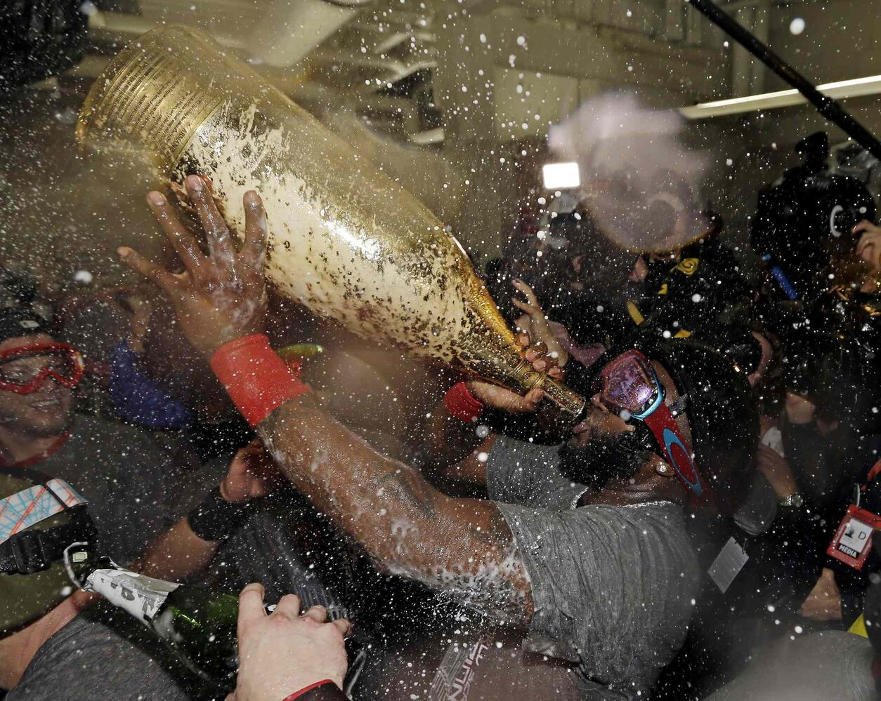 Boston Red Sox's David Ortiz drinks out of a giant bottle of Champagne as he celebrates with teammates.