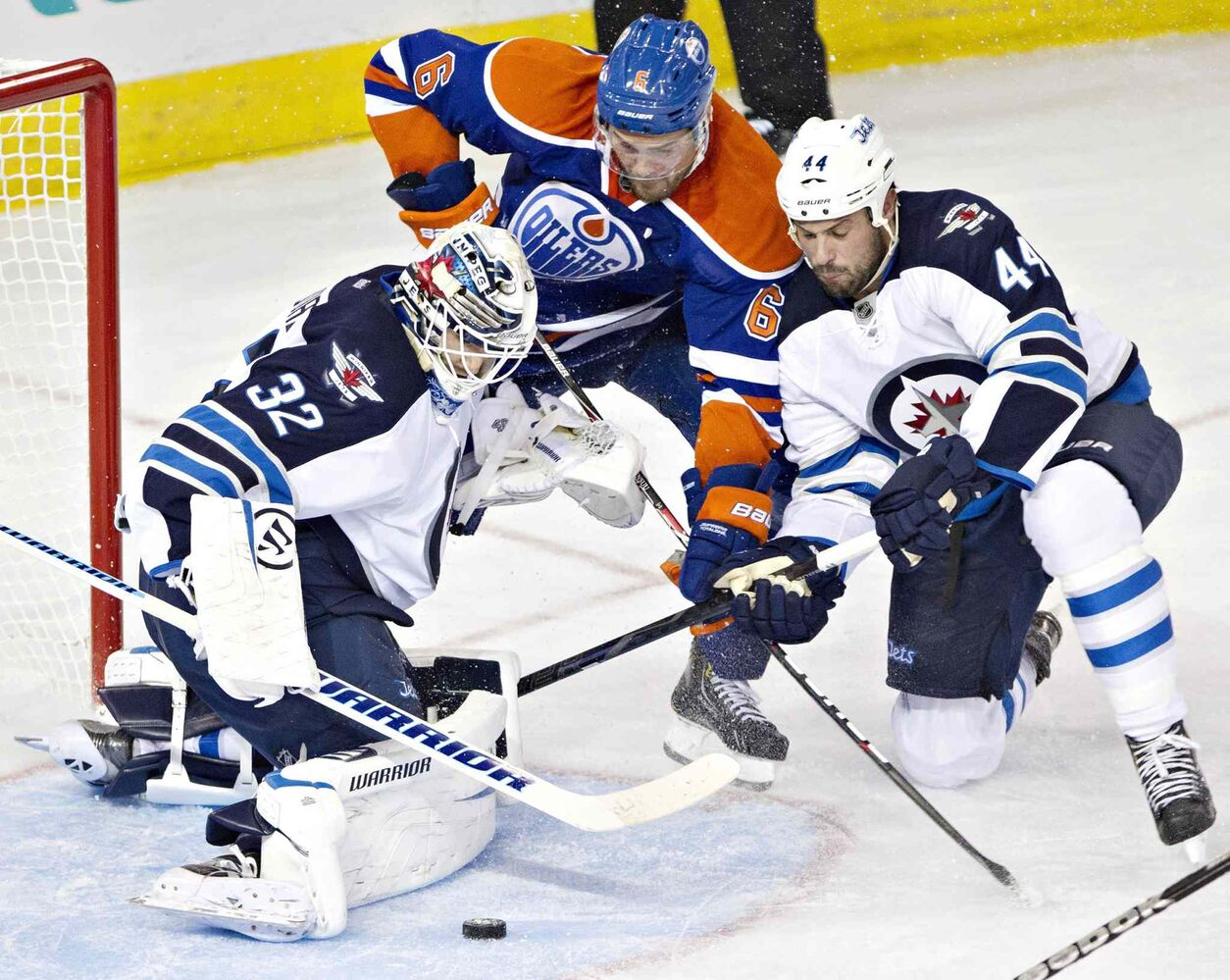 Winnipeg Jets goalie Edward Pasquale (32) makes a save as Zach Bogosian (44) and Edmonton Oilers Jesse Joensuu (6) battle for the rebound during the third period.