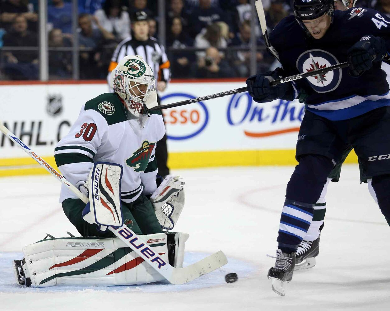 The Wild's Ilya Bryzgalov takes a stick to the mask from the Jets' Carl Klingberg during the second period. (TREVOR HAGAN / THE CANADIAN PRESS)