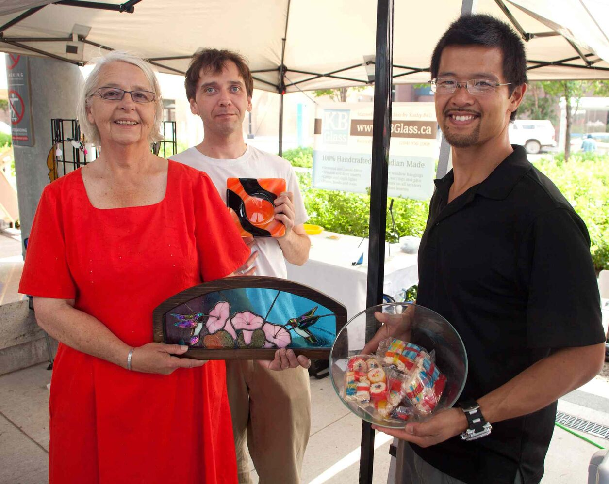 Unique products, baking and produce are available at the outdoor Downtown Farmer's Market at Manitoba Hydro Place. The market, organized by Downtown Winnipeg BIZ, is open from 10 a.m. to 3 p.m. every Thursday during the summer months, until mid-September. It then reverts to a monthly event indoors. Pictured, from left, are Kathy Bell, Joseph Dyer (kbglass.ca) and Jeff Poon (sweetcbakery.ca). (John Johnston / Winnipeg Free Press)