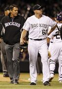 Colorado Rockies relief pitcher Rafael Betancourt, right, is escorted of the field by trainer Keith Dugger after Betancourt strained his groin while facing the Arizona Diamondbacks in the 10th inning of the Rockies' 5-4 victory in a baseball game in Denver on Tuesday, May 21, 2013. Betancourt was forced to leave the game after throwing only two pitches. (AP Photo/David Zalubowski)