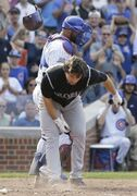 Colorado Rockies' Charlie Culberson, front, throws his helmet after being called out on strikes during the ninth inning of a baseball game against the Chicago Cubs in Chicago, Thursday, July 31, 2014. The Cubs won 3-1. (AP Photo/Nam Y. Huh)