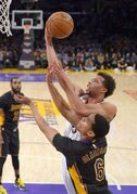 Milwaukee Bucks guard Michael Carter-Williams, top, shoots as Los Angeles Lakers guard Jordan Clarkson defends during the first half of an NBA basketball game, Friday, Feb. 27, 2015, in Los Angeles. (AP Photo/Mark J. Terrill)