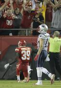 In this Sept. 29, 2014, photo, Kansas City Chiefs free safety Husain Abdullah, left, gets up in the end zone after dropping to his knees in prayer as New England Patriots wide receiver Julian Edelman, right, walks past after Abdullah intercepted a pass and ran it back for a touchdown during the fourth quarter of an NFL football game in Kansas City, Mo. The NFL said Tuesday, Sept. 30, that Abdullah should not have been penalized for unsportsmanlike conduct when he dropped to his knees in prayer after the interception. (AP Photo/Charlie Riedel)