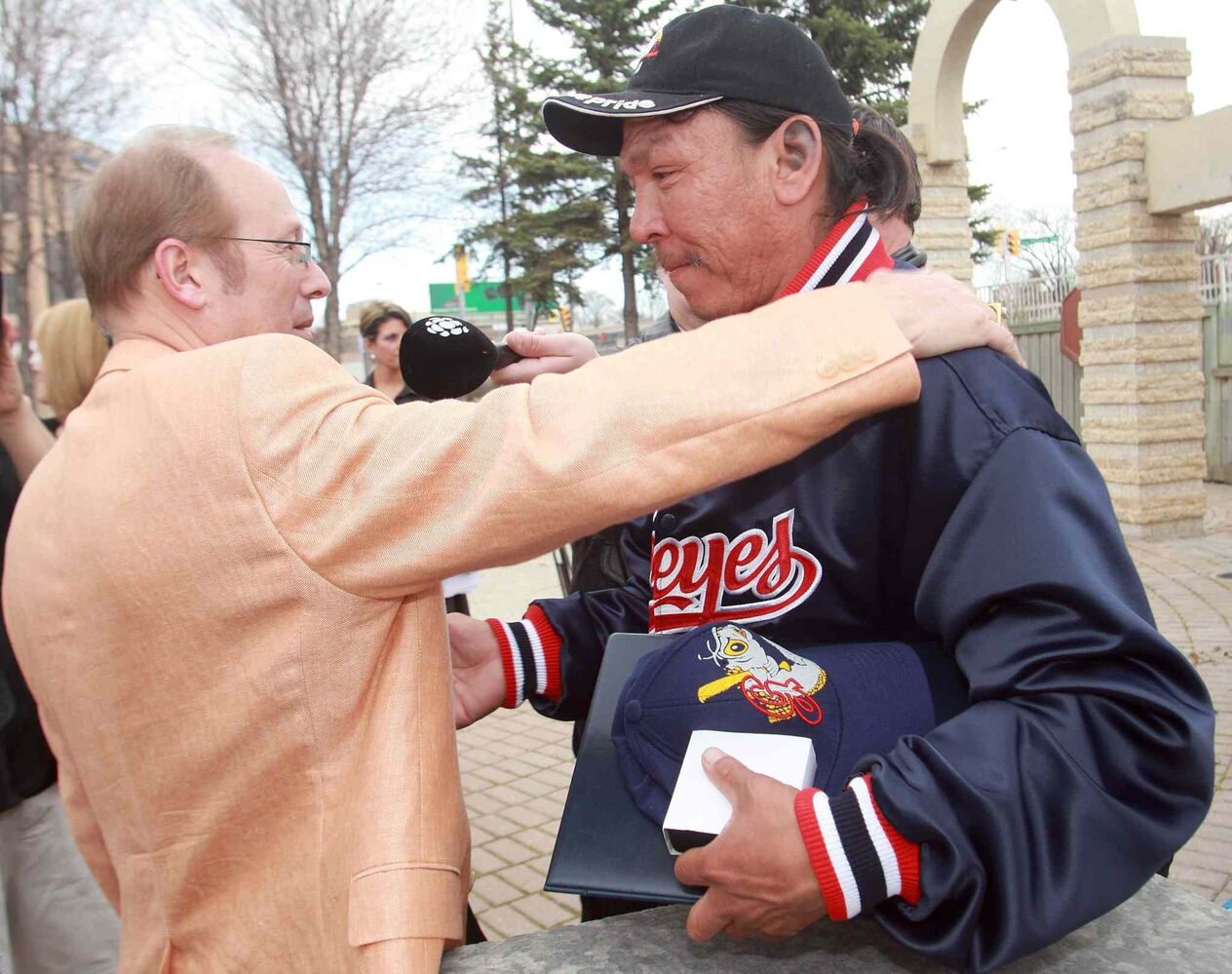May 6, 2009: Faron Hall gets a hug from mayor Sam Katz after Katz presented him with a City Of Winnipeg Medal, Goldeyes hat and  jacket, and a Goldeyes season ticket pass at a ceremony held  on the Red River Bank  near  the place where Faron saved a boy from drowning.