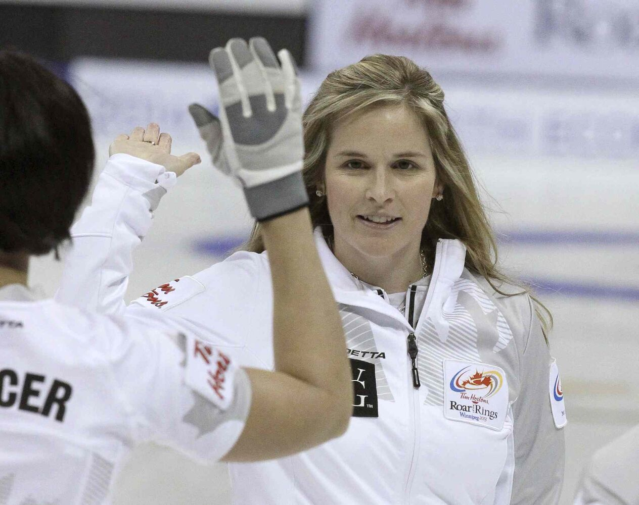 Skip Jennifer Jones high-fives teammate Jill Officer.