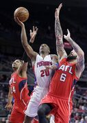 Detroit Pistons' Jodie Meeks (20) goes to the basket between Atlanta Hawks' Kent Bazemore (24) and Pero Antic (6) during the first half of an NBA basketball game Tuesday, March 31, 2015, in Auburn Hills, Mich. (AP Photo/Duane Burleson)