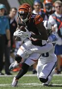 Cincinnati Bengals wide receiver A.J. Green (18) is tackled by Tennessee Titans cornerback Jason McCourty after catching a pass in the first half of an NFL football game, Sunday, Sept. 21, 2014, in Cincinnati. (AP Photo/Darron Cummings)