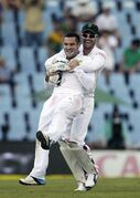 South Africa's bowler Dean Elgar, front, is carried by teammate AB de Villiers as he celebrates dismissing West Indies's captain Denesh Ramdin, for 14 runs on the third day of their 1st cricket test match at Centurion Park in Pretoria, South Africa, Friday, Dec. 19, 2014. (AP Photo/Themba Hadebe)