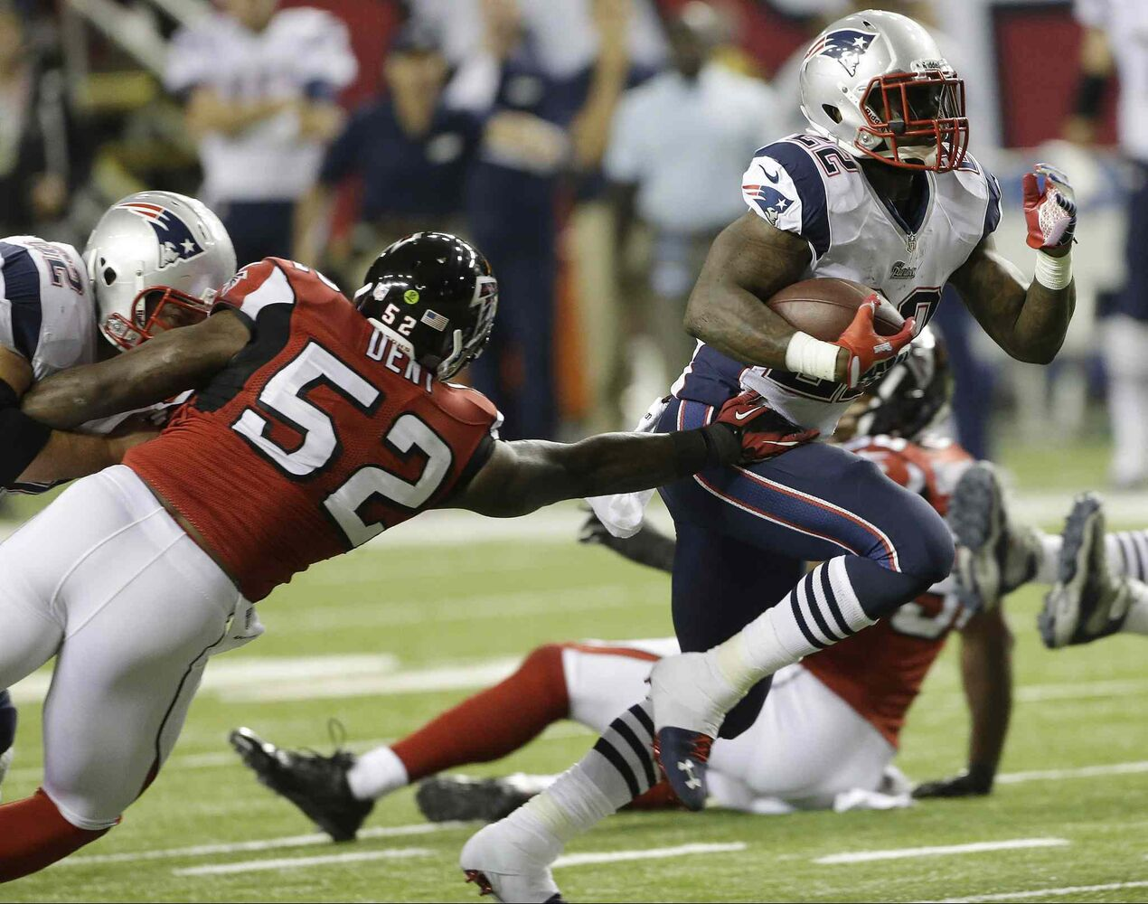 New England Patriots running back Stevan Ridley rushes past Atlanta Falcons linebacker Akeem Dent during the first half their game, Sunday, in Atlanta.  (John Bazemore / The Associated Press)