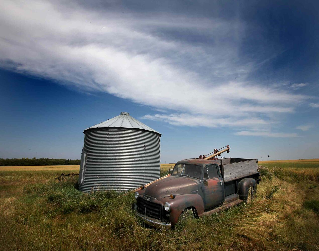 Gear from the past lays fallow field side near Sanford in late August. (Phil Hossack / Winnipeg Free Press)