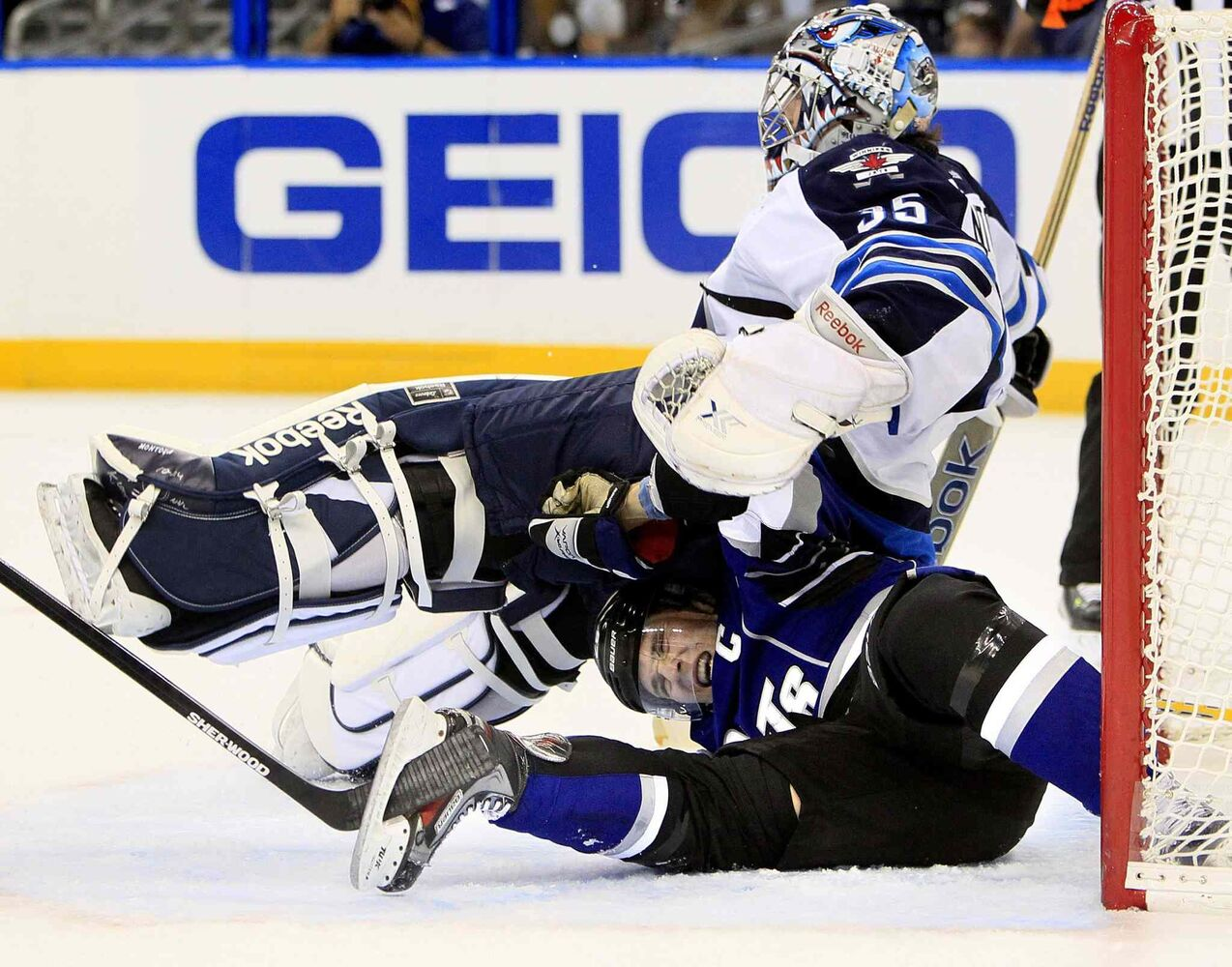 The Tampa Bay Lightning's Martin St. Louis (bottom) is crushed under Winnipeg Jets goalie Al Montoya in the crease during the first period.