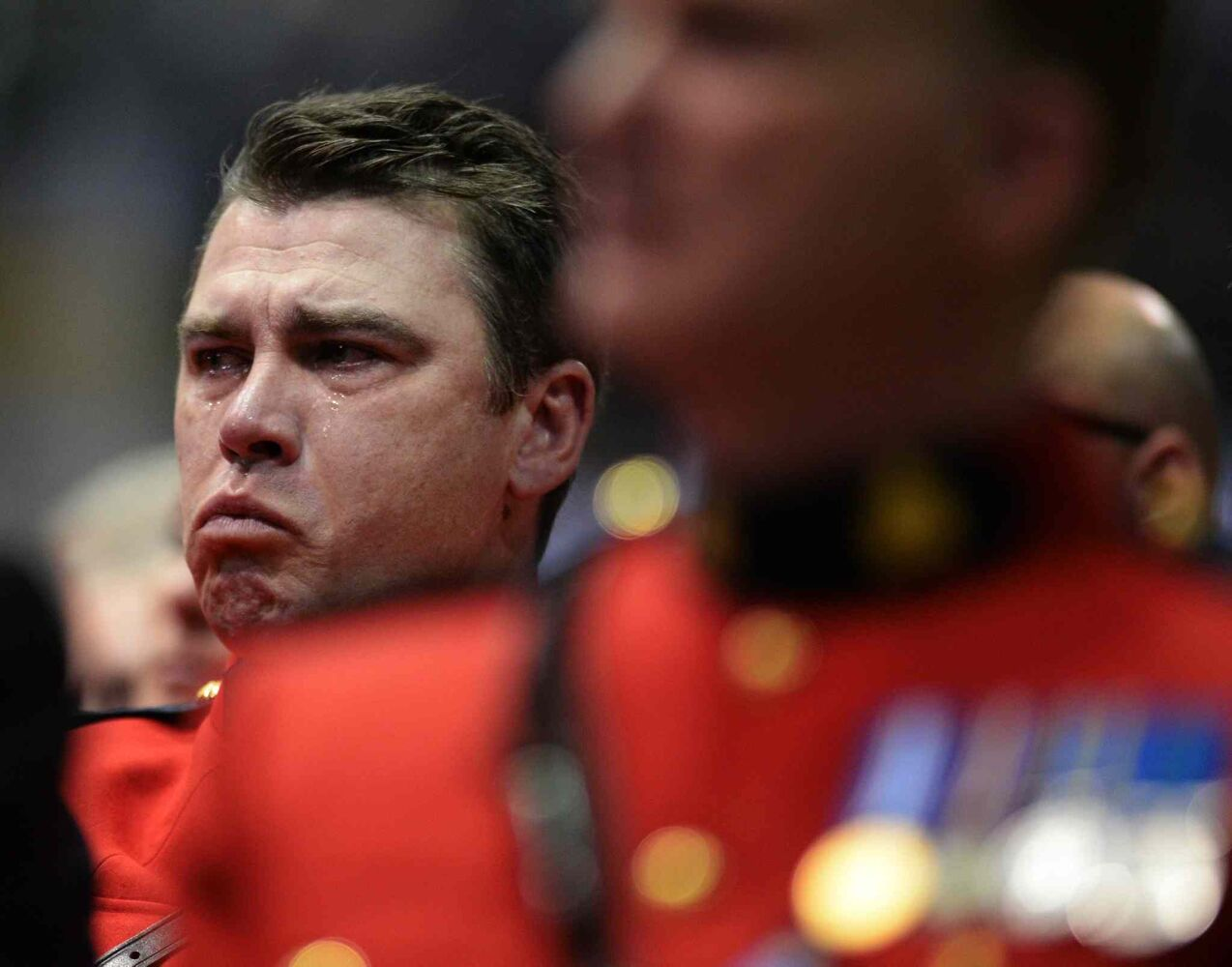 An RCMP officer tries to contain his emotions at the RCMP regimental funeral on Tuesday (Sean Kilpatrick / The Canadian Press)