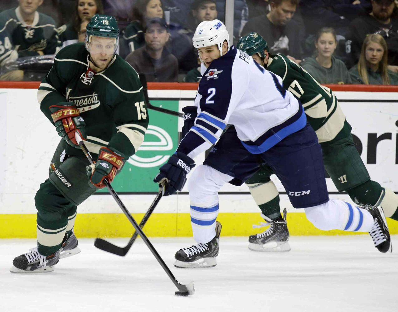 Minnesota Wild left wing Dany Heatley (left) controls the puck as Adam Pardy gives chase during the second period. (Ann Heisenfelt / The Associated Press)