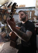 Jordon McConnell tries out one of his custom made acoustic guitars.