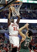 Chicago Bulls guard Jimmy Butler, left, goes up to shoot against Milwaukee Bucks center Zaza Pachulia during the second half in Game 1 of the NBA basketball playoffs Saturday, April 18, 2015, in Chicago. (AP Photo/Nam Y. Huh)