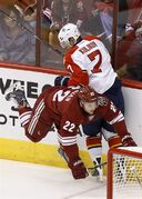 Arizona Coyotes' Brandon McMillan (22) falls to the ice after trying to check Florida Panthers' Dmitry Kulikov (7), of Russia, into the boards during the first period of an NHL hockey game Saturday, Oct. 25, 2014, in Glendale, Ariz. (AP Photo/Ross D. Franklin)