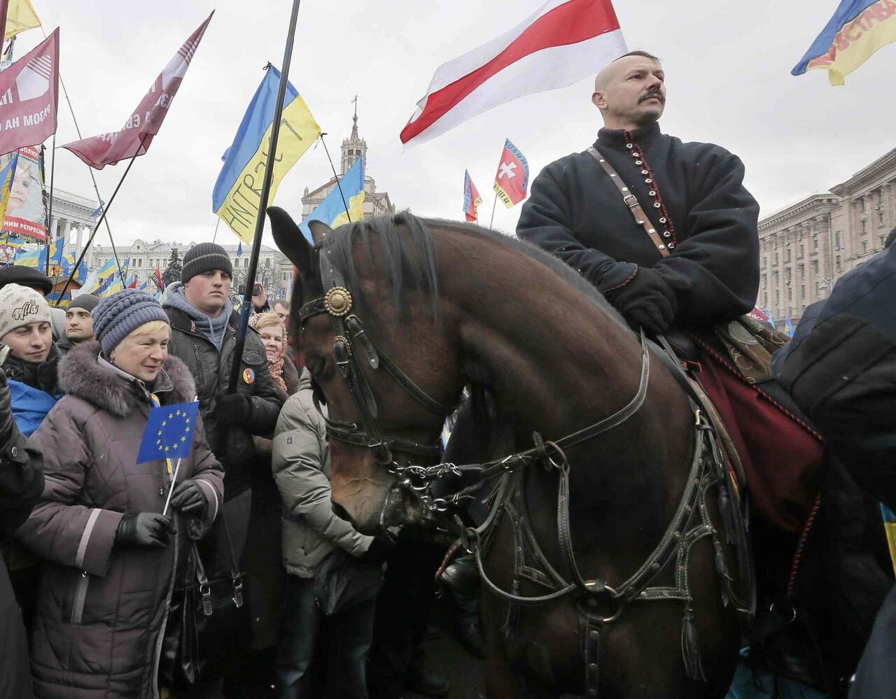 A man dressed as a Cossack on a horse pauses during a Pro-European Union rally in Independence Square. The third week of protests continued Sunday. (CP)