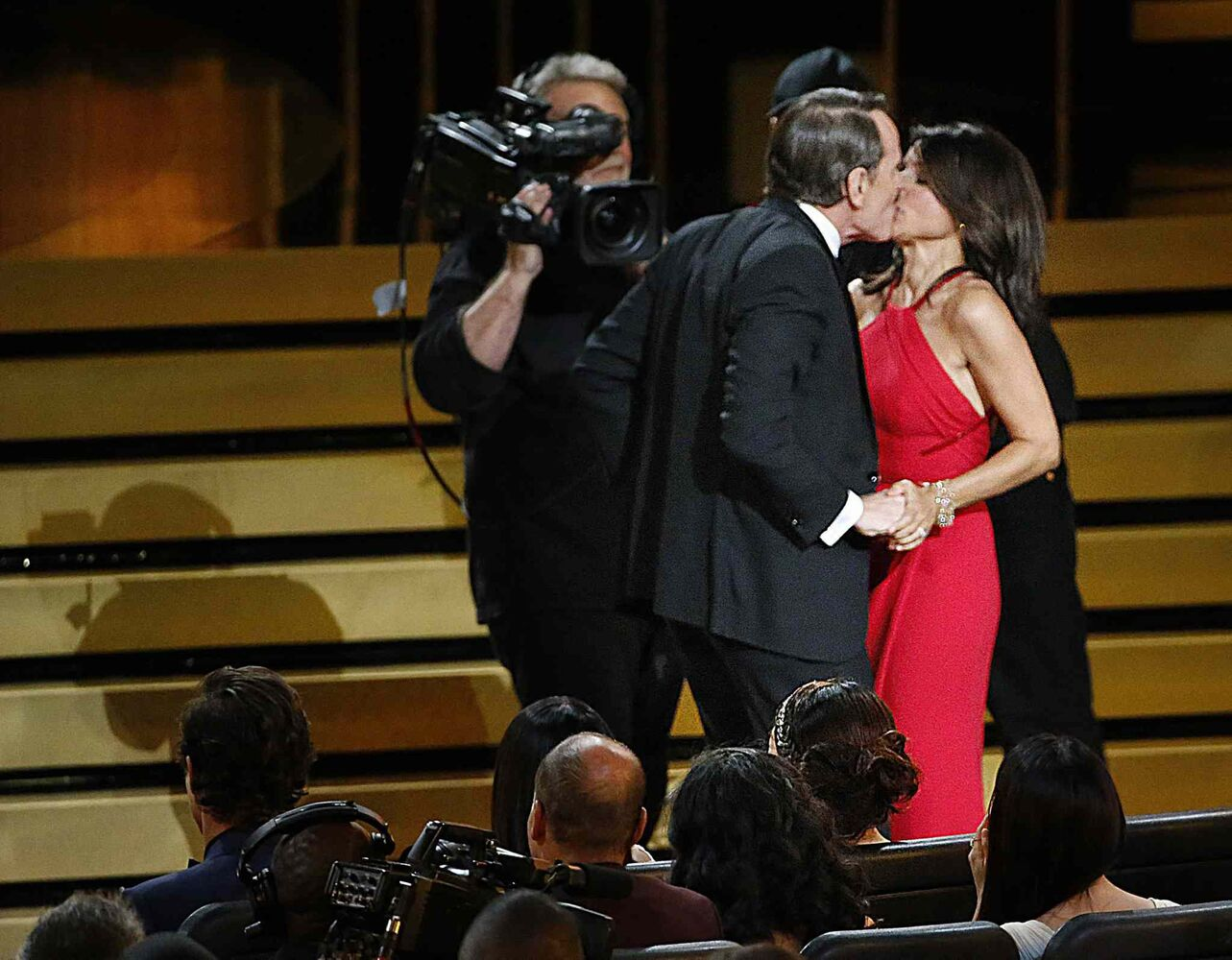 Julia Louis-Dreyfus, right, is kissed by Bryan Cranston during the 66th Annual Primetime Emmy Awards at Nokia Theatre at L.A. Live in Los Angeles Monday. (Tribune Media MCT)