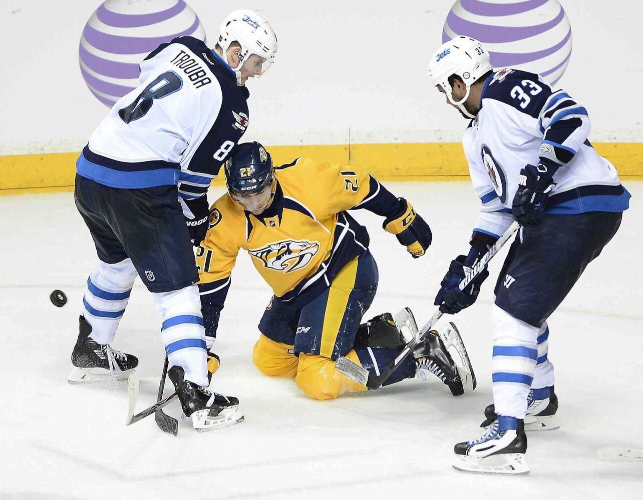 Winnipeg Jets' defenseman Jacob Trouba (8) and Dustin Byfuglien (33) knock the puck away from Nashville Predators' forward Simon Moser (21) in the third period. (Mark Zaleski / The Associated Press)