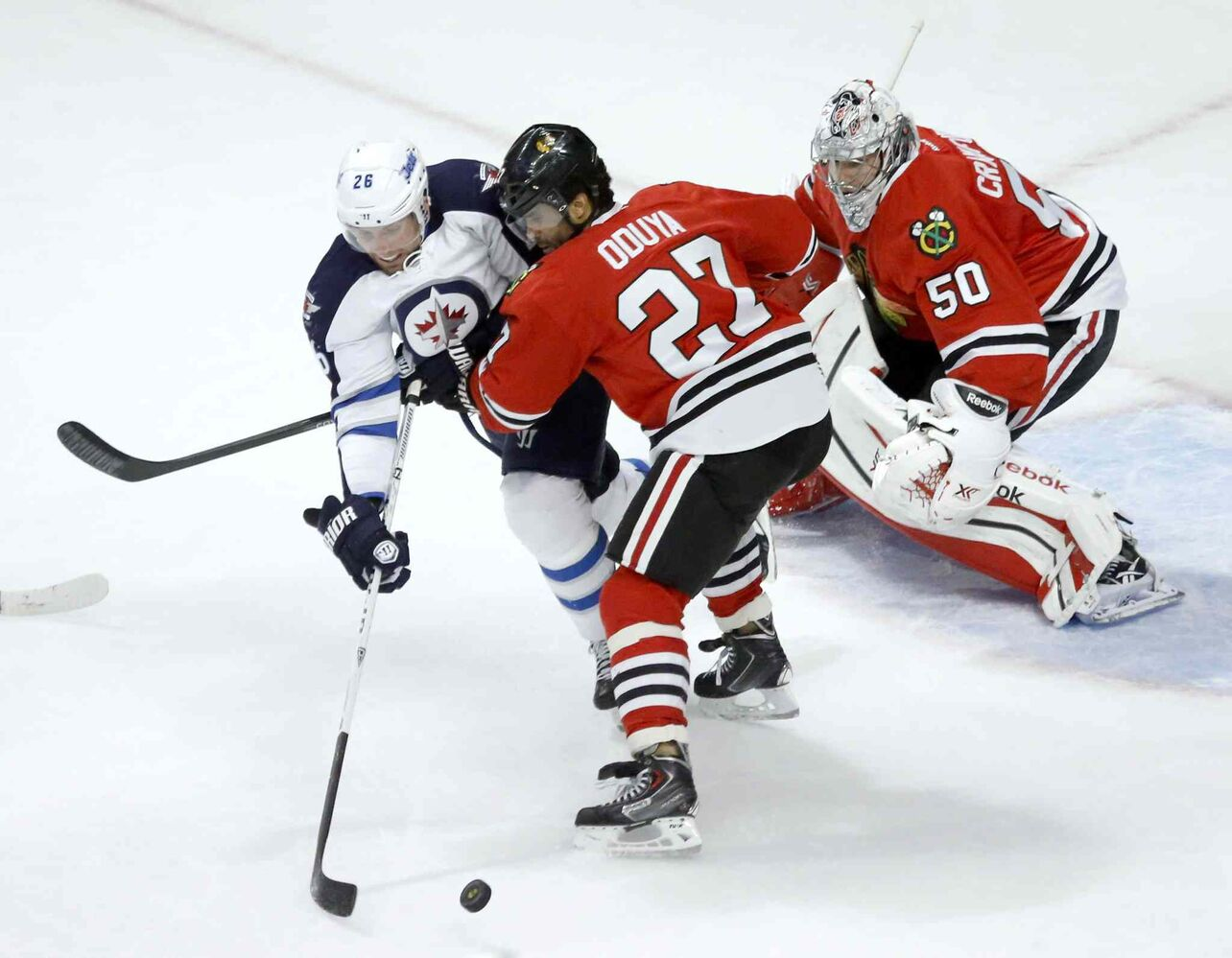 Blackhawks defenseman Johnny Oduya ties up Jets winger Blake Wheeler.