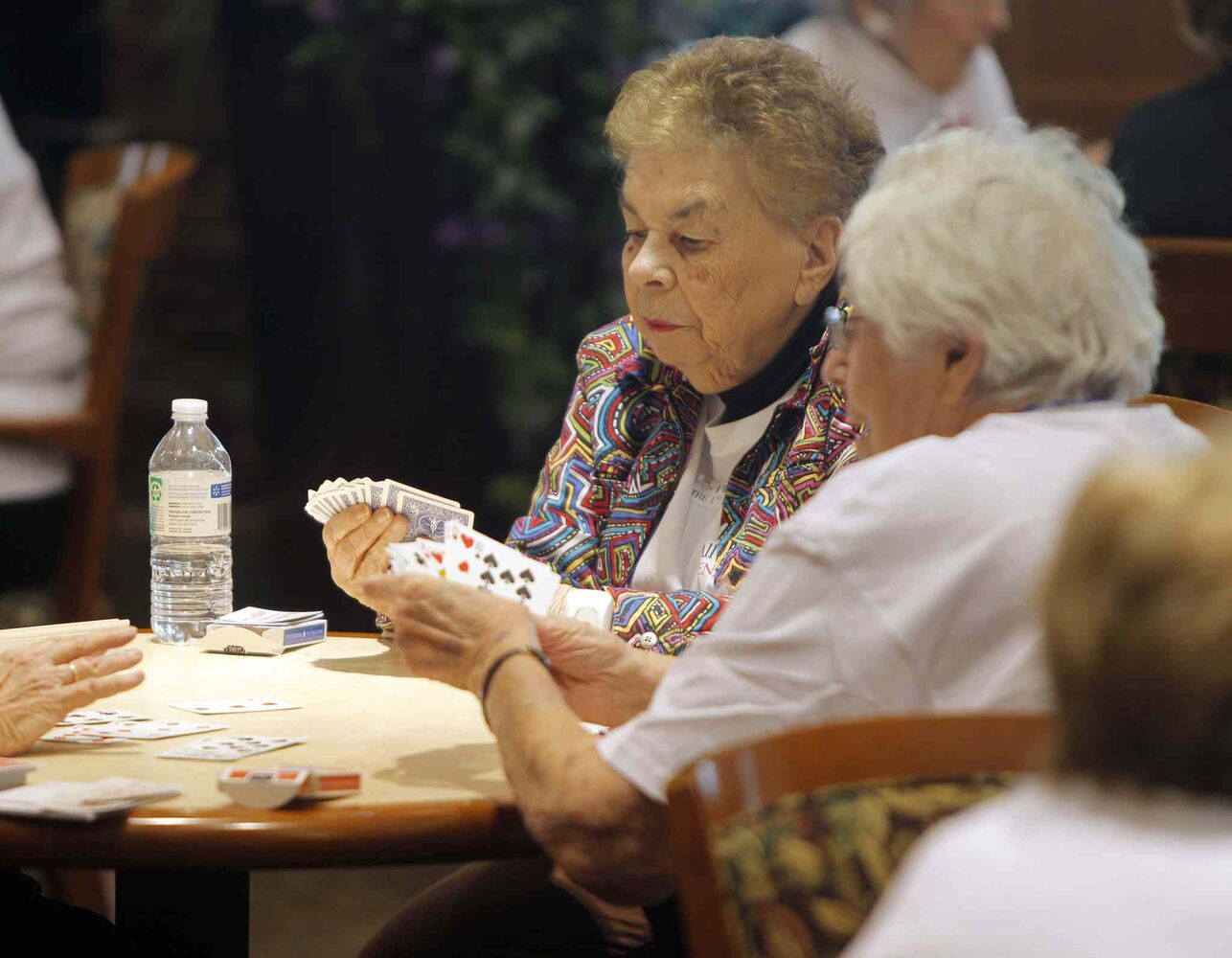 A pair of residents look at their cards at Shaftesbury Park Retirement Residence during a game of bridge. (Boris Minkevich / Winnipeg Free Press)