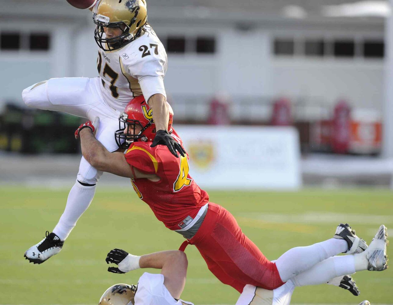 Kienan LaFrance (left) is tackled by Cory Roboch of the DInos during the first half. (Larry MacDougal / The Canadian Press)