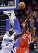 Orlando Magic's Kyle O'Quinn (2) and Houston Rockets' Tarik Black (10) go after a rebound during the first half of an NBA preseason basketball game in Orlando, Fla., Wednesday, Oct. 22, 2014. (AP Photo/John Raoux)