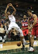 Milwaukee Bucks guard Giannis Antetokounmpo, left, is fouled by Washington Wizards forward Kris Humphries, right, during the second half of an NBA basketball game Saturday, Nov. 22, 2014, in Milwaukee. (AP Photo/Darren Hauck)