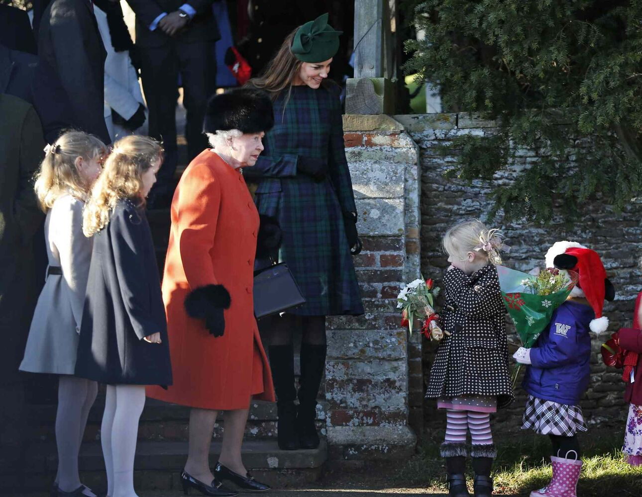 Britain's Queen Elizabeth II receives flowers from children as the Duchess of Cambridge looks on after members of the royal family attended a Christmas Day Service at St. Mary's church on the grounds of Sandringham Estate, the Queen's royal estate in Norfolk, England, Wednesday. (The Associated Press)