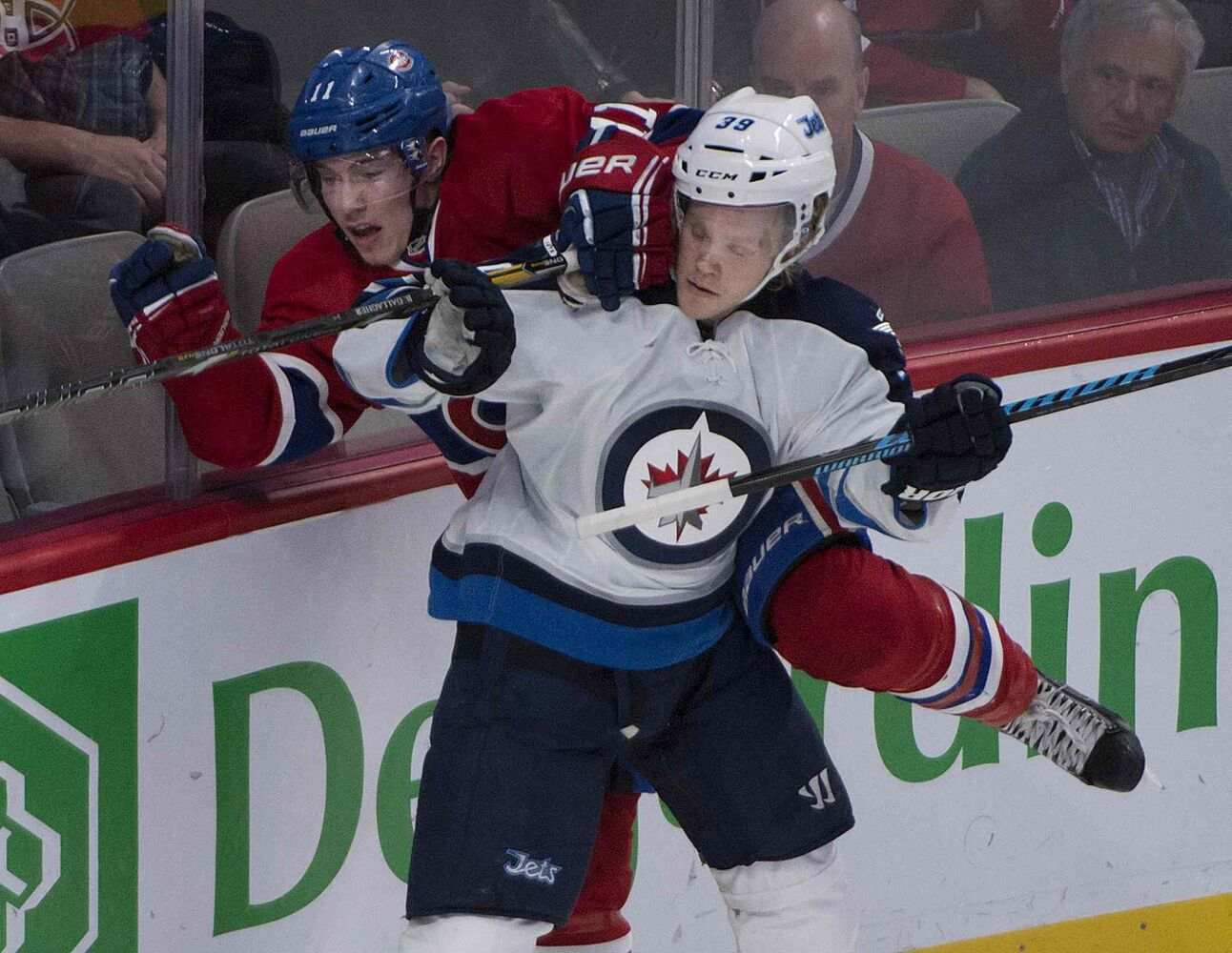 Jets defender Tobias Enstrom hammers Habs' forward Brendan Gallagher.  (Peter McCabe / The Canadian Press)