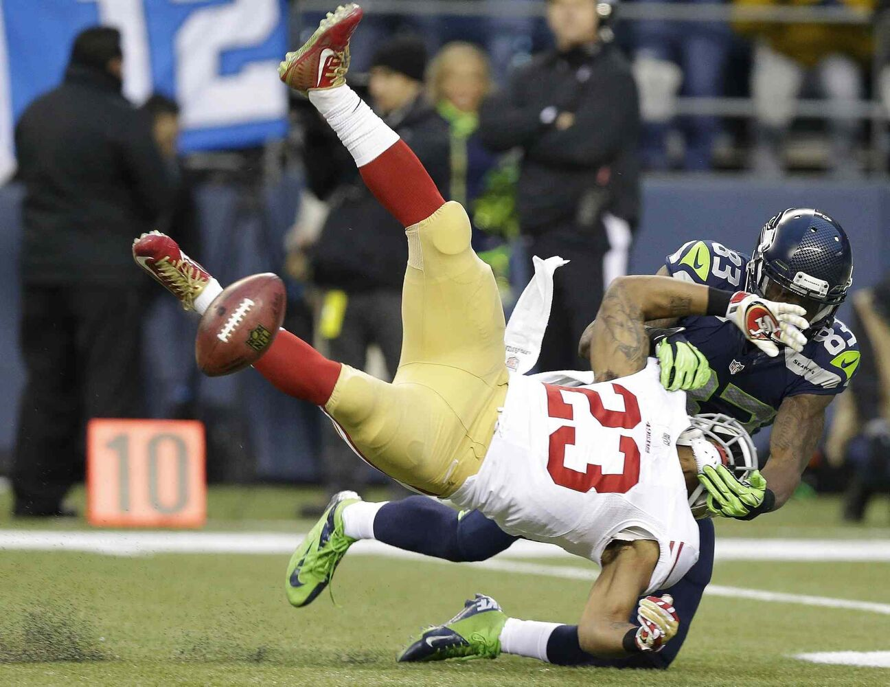 49ers' LaMichael James fumbles as he is hit by Seahawks Ricardo Lockette. (Elaine Thompson / The Associated Press)