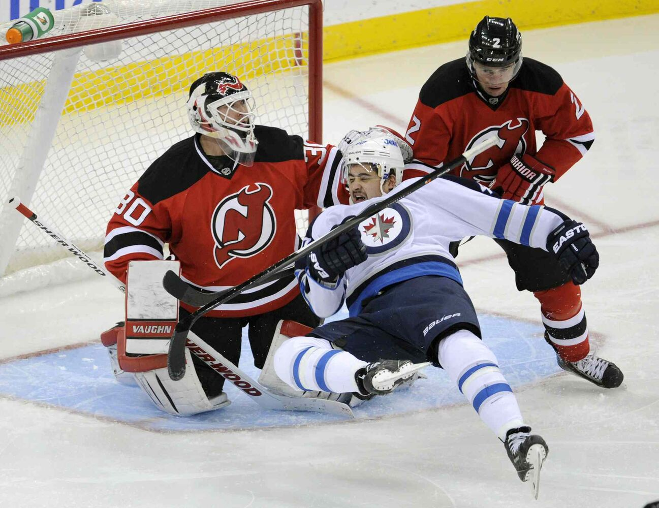 Winnipeg Jets forward Devin Setoguchi goes down after getting hit with the puck in front of New Jersey Devils goaltender Martin Brodeur and defenceman Marek Zidlicky during the third period. (BILL KOSTROUN / THE ASSOCIATED PRESS)