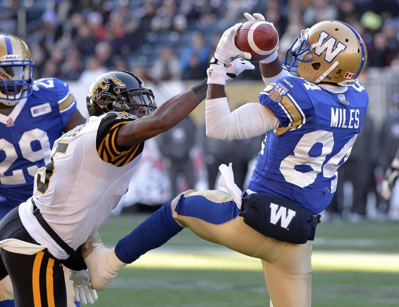 Winnipeg Blue Bombers' Wallace Miles (84) hauls a pass in as Dee Webb of the Hamilton Tiger-Cats reaches for the ball during the second half. (Fred Greenslade / The Canadian Press)